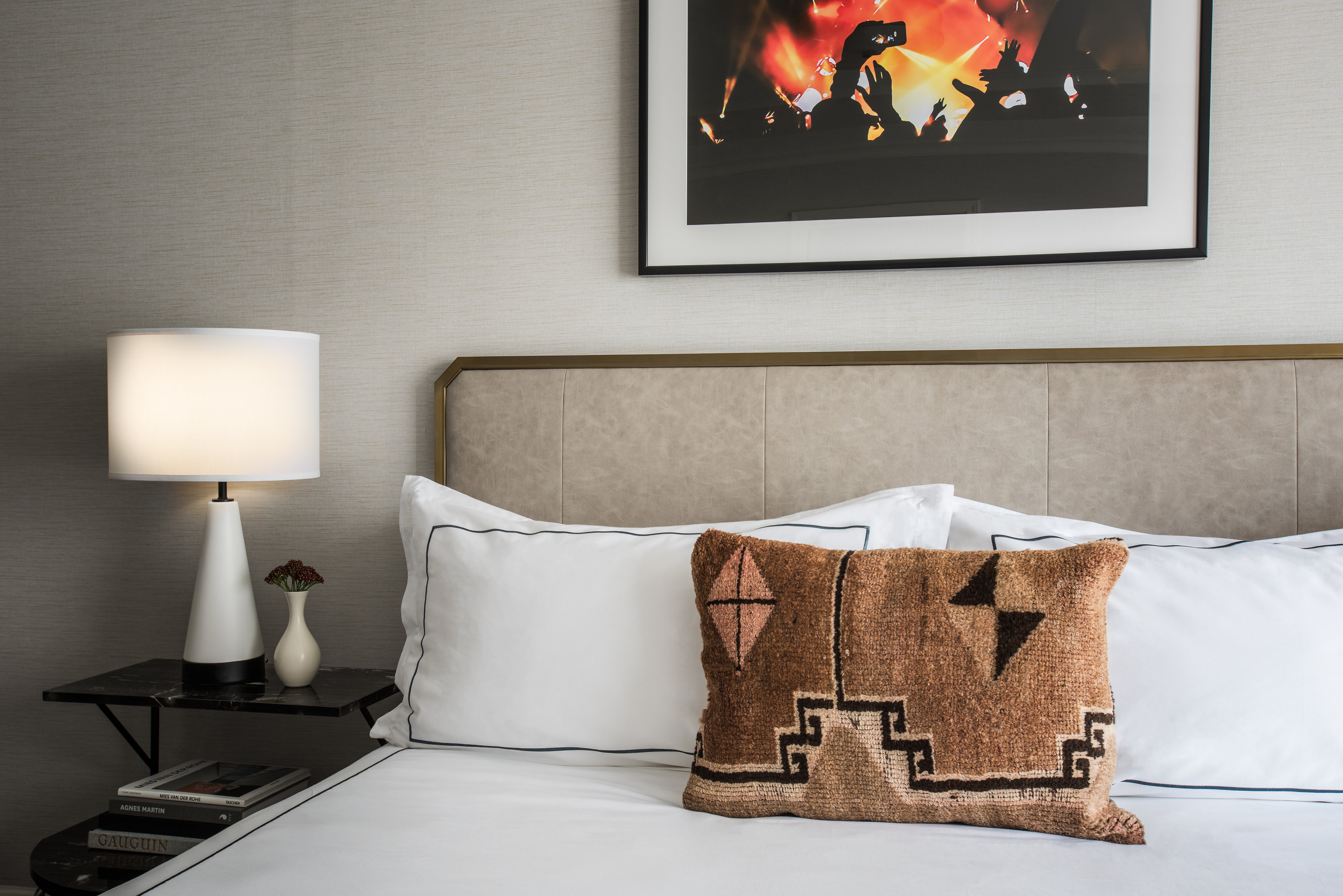 hotel bed with white linens and brown patterned pillow