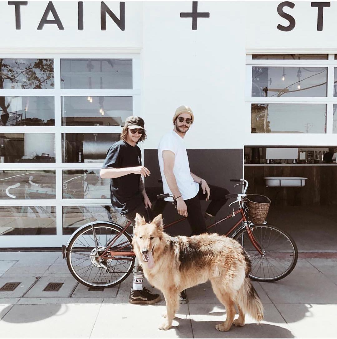 exterior view of cafe with two people on a bike and a dog